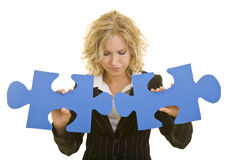 Trying to fit in. Blonde business woman trying to connect two oversized blue jigsaw pieces royalty free stock photos