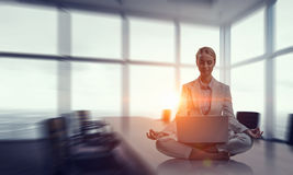 Trying to focus on positivity. Mixed media . Mixed media. Young attractive woman sitting cross legged lotus yoga pose at office table. Mixed media Royalty Free Stock Photography