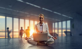 Trying to focus on positivity. Mixed media. Young attractive woman sitting cross legged lotus yoga pose at office table. Mixed media stock photos