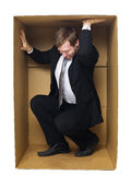 Trying to get out. Well dressed businessman in a tight cardboard box  on white background Royalty Free Stock Photos