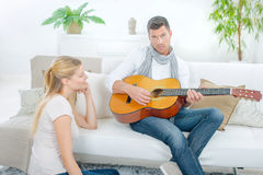 Trying to impress girlfriend by playing guitar Stock Photo