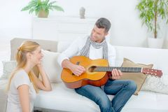Trying to impress girlfriend by playing guitar Stock Image