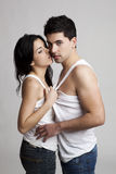 Trying to kiss. Sexy young couple isolated on a gray background Stock Photography