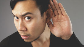 Trying to listen. An asian man with black t-shirt stock photography