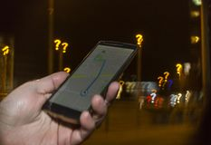 Trying to navigate in the city at night. Lost in the city concept. Hand holding phone with map on the screen and question mark bokeh in the background royalty free stock photo