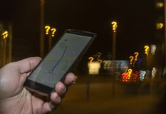 Trying to navigate in the city at night. Lost in the city concept. Hand holding phone with map on the screen and question mark bokeh in the background royalty free stock image