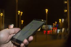 Trying to navigate in the city at night. Lost in the city concept. Hand holding phone with map on the screen and question mark bokeh in the background royalty free stock images