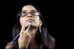 Trying to Remember. An Indian teenager with a pen trying to remember the answer of a question during her exam, on black studio background Royalty Free Stock Images