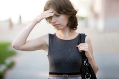 Trying to remember. Portrait of young office woman walking on the street in summer, frowning, holding her head with hand, businesswoman has forgotten something royalty free stock photos
