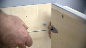 Trying to screw a screw into the wardrobe frame. Two men are assembling new furniture in freshly painted room. They use compact cordless drill-driver, hammer and stock footage