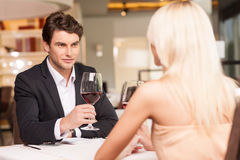 Trying to seduce. Attractive men with wine glass looking at beautiful woman Royalty Free Stock Photography