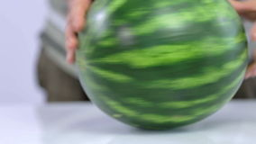 Trying to spin watermelon in circles with man standing in back. Watermelon is rolled around it's axis on white background stock video