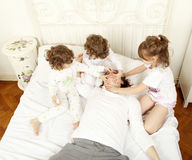 Trying to stop a man to snore. Children trying to stop her father to snore Royalty Free Stock Images