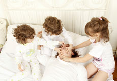 Trying to stop a man to snore. Children trying to stop her father to snore Royalty Free Stock Image