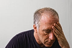Trying to think. Beautifully detailed real portrait of weathered looking adult white man holding forehead with eyes closed Royalty Free Stock Image
