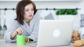 Trying to wake up. Sleepy woman stirs a coffee in the cup and periodically fall asleep, work with laptop stock footage