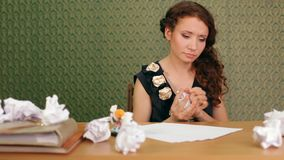 Trying To Write A Letter. Beautiful girl sitting at a table writing a letter. Moving camera stock video footage
