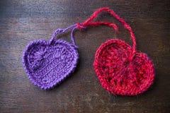 Trykotowa czerwień i purpurowe serca na drewnianym tle Fotografia Stock