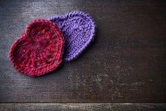 Trykotowa czerwień i purpurowe serca na drewnianym tle Fotografia Royalty Free