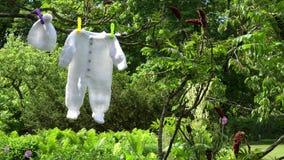 Trykotowego białego dziecka odzieżowy ciało i kapeluszowy zrozumienie na gałąź w ogródzie zbiory