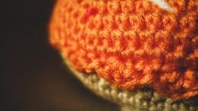 Trykotowy pomarańczowy pączek z opatrunkiem na tle pudełka zbliżenie Handmade dla dzieci bawić się w kawiarni lub sklepie zdjęcie stock
