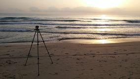 Trypod de photographe faisant face à de sunrise Images stock