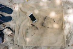 Trzepnięcie klapy, okulary przeciwsłoneczni, ręcznik na plaży Fotografia Royalty Free