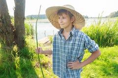 Trzyćwierciowy widoku portret relaksujący wędkarza nastoletni chłopak jest ubranym szkockiej kraty koszula i słomianego kapelusz Zdjęcia Stock