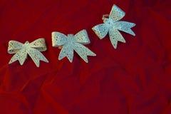 Trzy łęku na ognistym czerwonym tle dla nowego roku i bożych narodzeń Zdjęcia Royalty Free