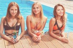 Trzy ładnej dziewczyny z koktajlami przy basenem obraz royalty free
