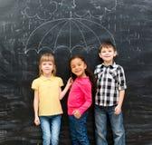 Trzy śmiesznego dziecka z parasolem rysującym na blackboard fotografia royalty free