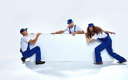 Trzy śmiesznego rzemieślnika trzyma pustą deskę Obraz Stock