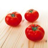 Trzy Świeżego dojrzałego pomidoru na drewno stole Zdjęcia Stock