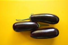 Trzy świeżej czarnej organicznie oberżyny na żółtym tle, odgórny widok obrazy royalty free