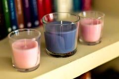 Trzy świeczki na półce z tło książkami fotografia royalty free