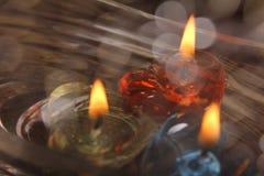 Trzy świeczki unosi się na wodnym pucharze z bokeh ef fotografia stock