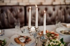 Trzy świeczki w eleganckim świeczka właścicielu dekoruje stół Zdjęcia Royalty Free