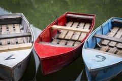 Trzy świetlanobarwnej cumującej łodzi na jeziorze Obrazy Royalty Free