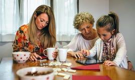Trzy żeńskiego pokolenia używać pastylkę i smartphone Obraz Royalty Free