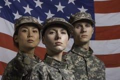 Trzy żołnierza pozującego przed flaga amerykańską, horyzontalną fotografia stock