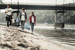 Trzy aktywnego ucznia cieszy się zgłaszać się na ochotnika ogromnie podczas gdy czyścić plażę zdjęcia royalty free
