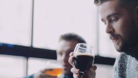 Trzy atrakcyjnego młodego człowieka w przypadkowej odzieży clinking piwnych kubki i szczęśliwie piją piwo Weekendowe aktywność, b zbiory wideo