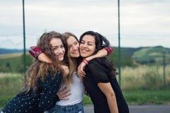 Trzy atrakcyjnej nastoletniej dziewczyny outdoors na boisku Obrazy Stock