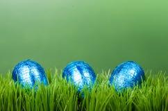 Trzy błękita foliowego Wielkanocnego jajka na trawie Zdjęcia Royalty Free