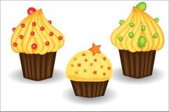 Trzy babeczki z żółtą śmietanką, jagodami i proszkami, Cukierki, deser Obraz Royalty Free