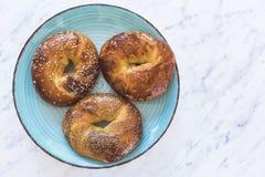 Trzy bagels na błękitnym talerzu z marmurowym tłem fotografia stock