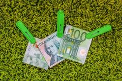 Trzy 100 banknotów zielonego euro 100 szwedzkich crownes i 200 szwedzkich crownes w zielonych odzieżowych czopach przy zielonym t Zdjęcia Stock