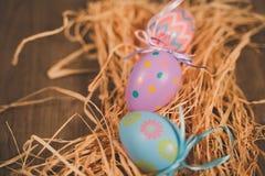 Trzy barwionego Easter jajka na łóżku słoma obrazy stock