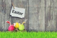 Trzy barwionego Easter jajka na drewnianym tle zdjęcie royalty free