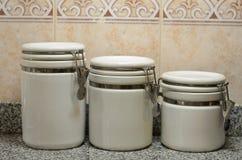 Trzy białego ceramicznego słoju na kuchennym kontuarze Zdjęcia Royalty Free